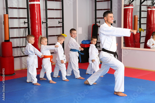 Photo Stands Martial arts Male karate instructor training little children in dojo