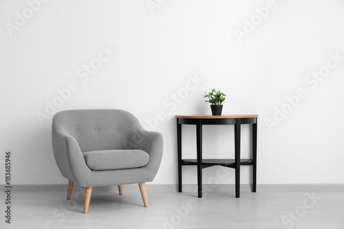Obraz na plátne Comfortable armchair and table near light wall