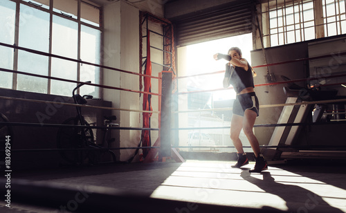Female boxer training inside a boxing ring - Buy this stock