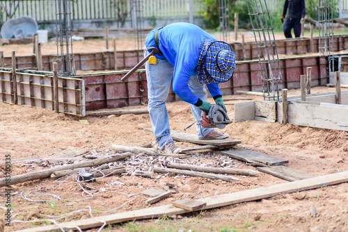 Fototapety, obrazy: The worker holding wood cutter and cutting wood on the ground at construction site