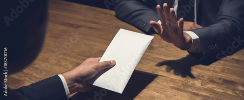 Fotografía Businessman rejecting money in white envelope offered by his partner in the dark