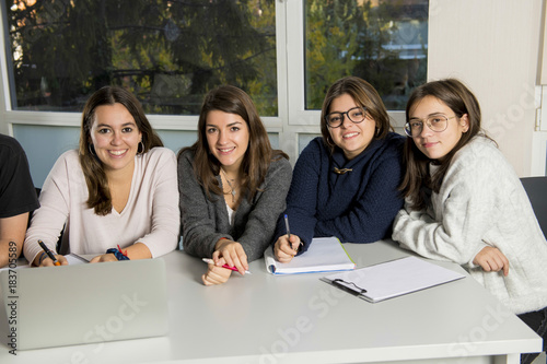 group of young male and female teenager university students at school sitting on classroom learning and working on project together