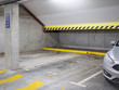 Parkplatz in einer Tiefgarage mit Betonwänden und gelben Warnstreifen
