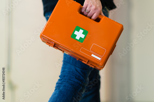 Photo Man with first aid kit runs to help