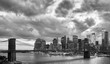 Black and white picture of Manhattan and Brooklyn Bridge with dramatic cloudscape at dusk, New York, USA.