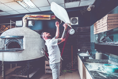 Foto auf AluDibond Pizzeria Bearded pizzaiolo chef lunching dough into air