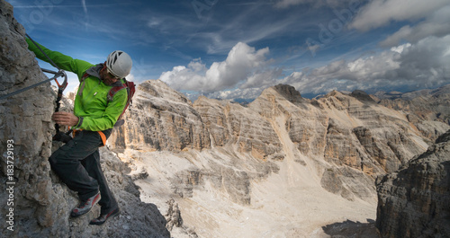 male mountain climber in a green jacket on an exposed Via Ferrata in the Dolomites in Italy with a great view of the surrounding landscape