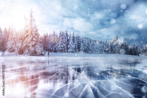 Fotobehang Bergen Blue ice and cracks on the surface of the ice. Frozen lake in winter mountains. It is snowing. The hills of pines. Winter. Carpathian Ukraine Europe