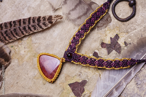 Fotografie, Obraz  Natural gemstone handmade macrame meterial necklace with wild feather background