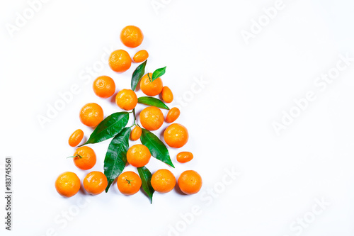 Christmas tree made from fresh mandarin with leaves on a white background. Ripe delicious fruit. Symbol of the New Year and Christmas