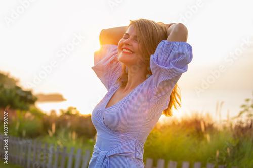 Fotografia Happy woman enjoying life outdoors at sunset
