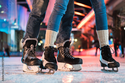 Fototapeta close-up partial view of young couple in skates ice skating on rink