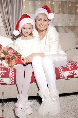 Photo Mama i córka na kanapie podczas Świąt Bożego Narodzenia z prezentami