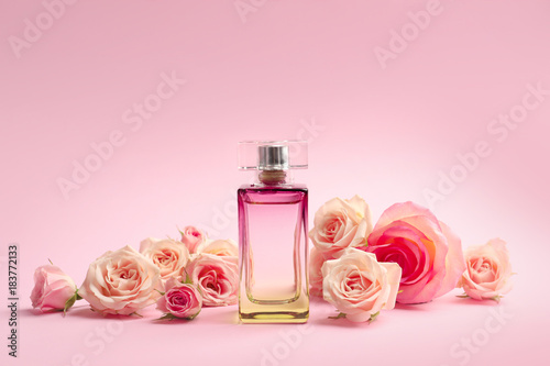 Fototapeta Bottle of perfume with flowers on color background obraz
