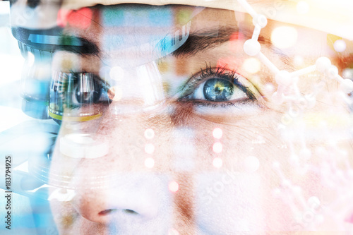 Smart scientist technology concept. Double exposure of microscope , science equipment glasses, selective focus on European eye and atom graphics with flare light effect.