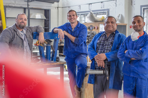 Portrait of male car mechanic team in repair garage