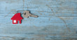 Key with house icon on wooden background