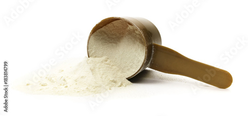 Fotografia Spilled measuring cup of protein powder on a white background.