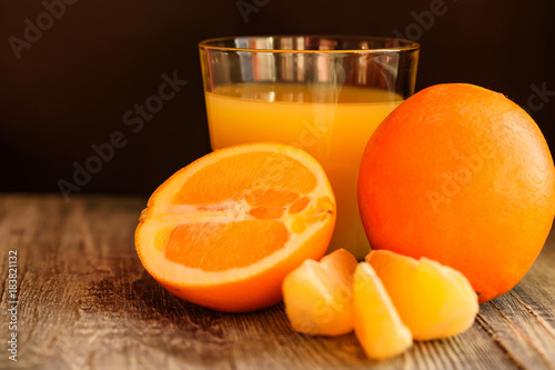 Poster Sap Oranges and orange juice on a wooden background