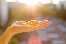 Hand Of A Woman Holding Fish Oil Omega-3 Capsules, Urban Sunset Background. Healthy Eating, Medicine, Health Care, Food Supplements And People Concept