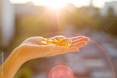 Fototapeta Hand of a woman holding fish oil Omega-3 capsules, urban sunset background. Healthy eating, medicine, health care, food supplements and people concept obraz
