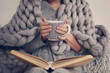 canvas print picture - Cozy Woman covered with warm soft merino wool blanket reading a book. Relax, comfort lifestyle.