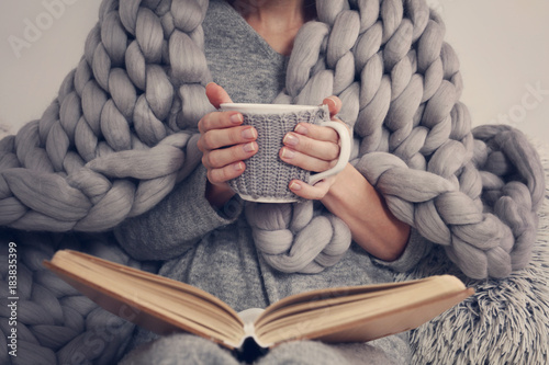 Obraz Cozy Woman covered with warm soft merino wool blanket reading a book. Relax, comfort lifestyle. - fototapety do salonu