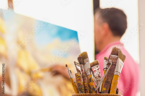 Photo Close up of wooden flask with paint brushes, with blurred man painting as backgr