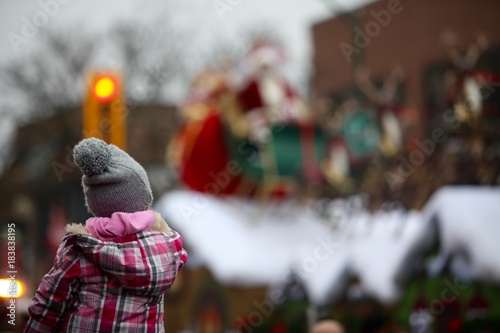 Fototapeta Young girl on fathers shoulders watching santa claus on his sleigh in a parade
