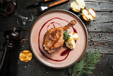 beautiful serving duck leg confit with apples and berry sauce on a wooden plate with a glass of red wine - 183857397