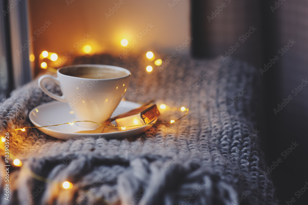 Fototapety, obrazy: cozy winter or autumn morning at home. Hot coffee with gold metallic spoon, warm blanket, garland and candle lights, swedish hygge concept.