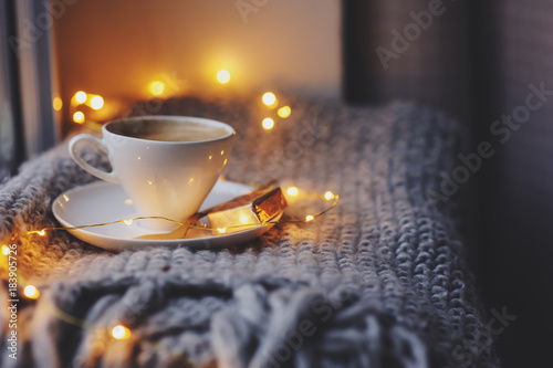 Obraz cozy winter or autumn morning at home. Hot coffee with gold metallic spoon, warm blanket, garland and candle lights, swedish hygge concept. - fototapety do salonu