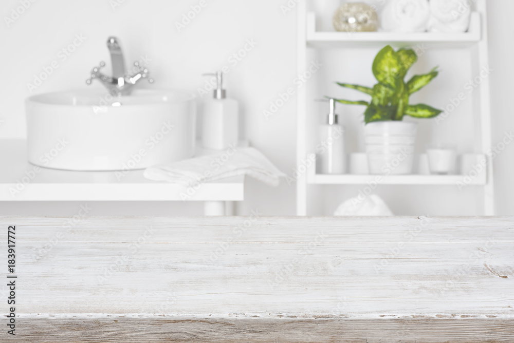 White Bathroom Shelves | Wooden Table In Front Of Blurred White Bathroom Shelves Background
