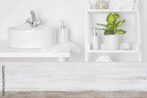 Fotografía  Wooden table in front of blurred white bathroom shelves background