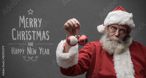 Lazy Santa Claus holding Christmas balls Wallpaper Mural