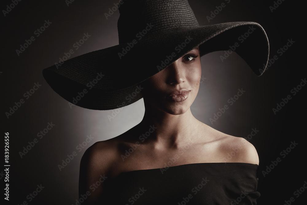 Fototapeta Dark studio portrait of elegant sexy woman in black wide hat and black dress.