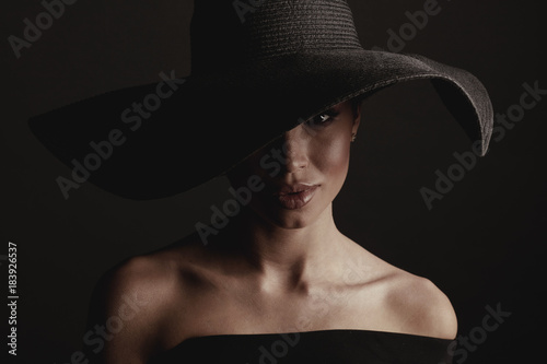 Fototapety, obrazy: Dark studio portrait of elegant sexy woman in black wide hat and black dress.