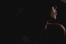 Dramatic Dark Studio Portrait Of Elegant And Sexy Woman In Black Wide Hat And Black Dress. Hidden Eyes.