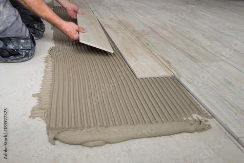 Fotografía  Keramische Fliesen in Holzoptik werden am Boden verlegt
