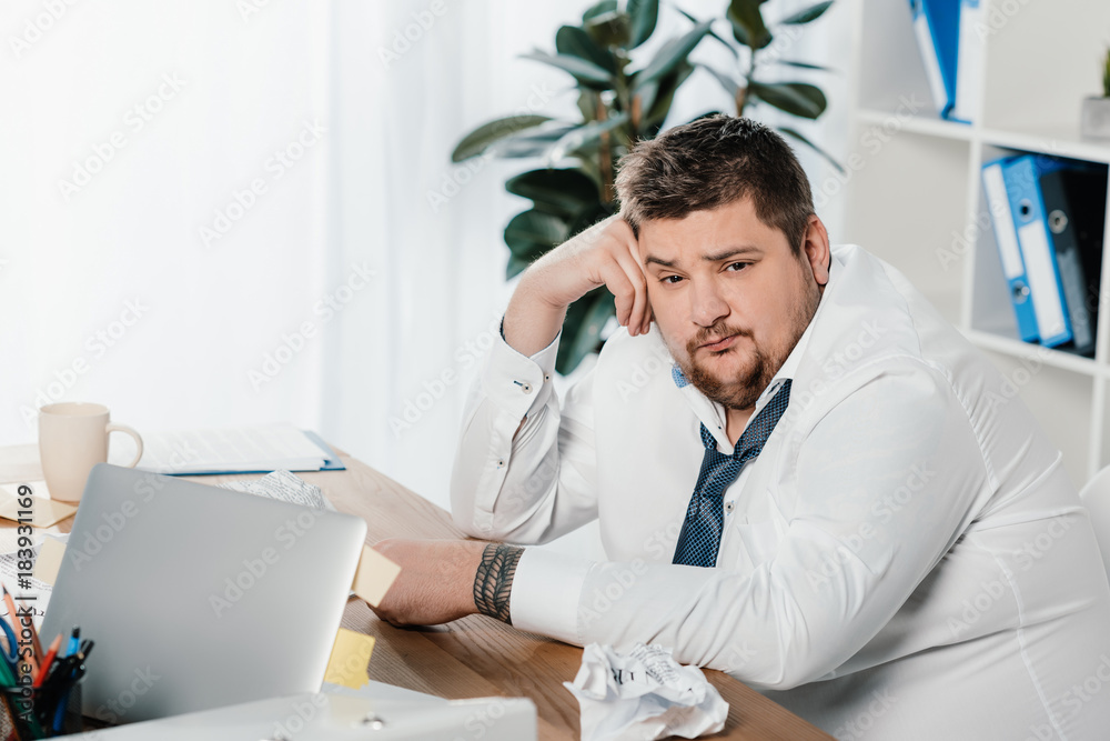 Fototapeta fat businessman sitting at workplace with crumpled papers and laptop