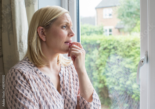Sad Woman Suffering From Agoraphobia Looking Out Of Window Wallpaper Mural