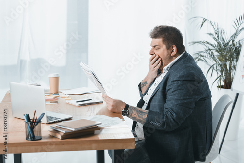 Photo overweight yawning businessman in suit reading newspaper at workplace