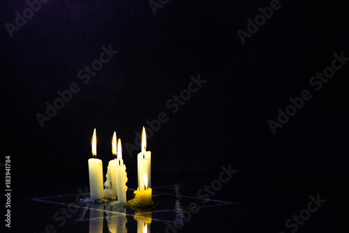 Obraz Five burning candles and the Star of David against a black background. - fototapety do salonu
