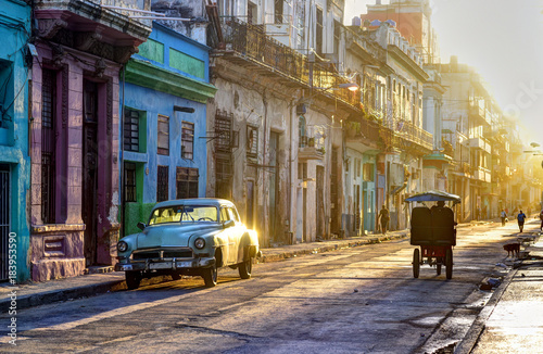 Street scene in Old Havana (La Habana Vieja), classic car, bicitaxi and people going to work, Cuba