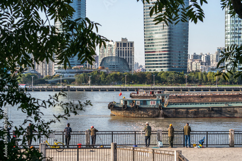 Fishermans on Huangpu river with skyline view of Shanghai skyscraper, China Poster