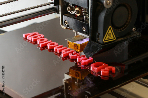 3D printer printing the words 3D technology in red letters, close up of the machine