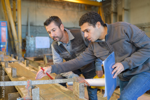 carpenter with apprentice in training period Canvas Print