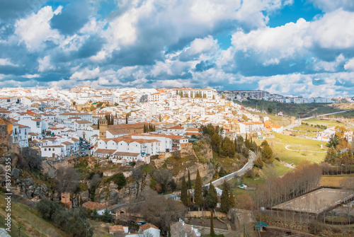 Fotografía  Aerial panoramic view of Ronda, tradational white houses with tile roofs on the hill and its surroundings, one of most famous white villages (pueblos blancos) in Malaga province, Andalusia, Spain