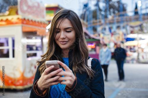 Staande foto Amusementspark Young woman using mobile phone inside an amusement park