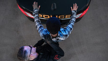 A Suspect Is Searched By A Police Officer At The Rear Of His Cruiser